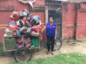 Müllsammlerin mit mit Plastikflaschen beladenem Dreirad